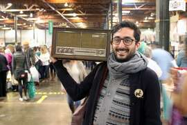 A happy shopper poses with his find from the electronics department at a past Oakland Museum White Elephant Sale.