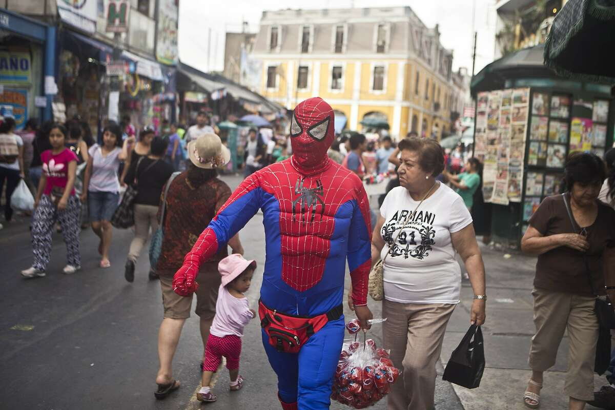 SAY IT AIN'T SO, SPIDEY: Not only is Spider-Man in terrible shape (his abs are where his pecs should be), but he's wearing a fanny pack. Still, he's able to turn a youngster's head in Lima, Peru.