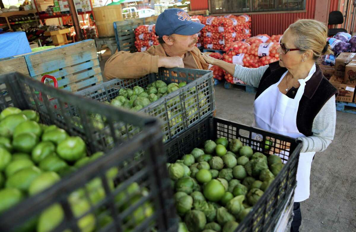Vendor Rogelio Valdez discusses tomatillos with Irma Galvan, owner of Irma's restaurant downtown, as she shops at a market on Airline Drive. Galvan is working with Sysco to increase its selection of spices.