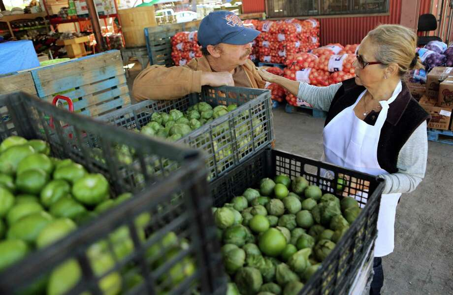 Vendor Rogelio Valdez discusses tomatillos with Irma Galvan, owner of Irma's restaurant downtown, as she shops at a market on Airline Drive. Galvan is working with Sysco to increase its selection of spices. Photo: Mayra Beltran, Staff / © 2015 Houston Chronicle