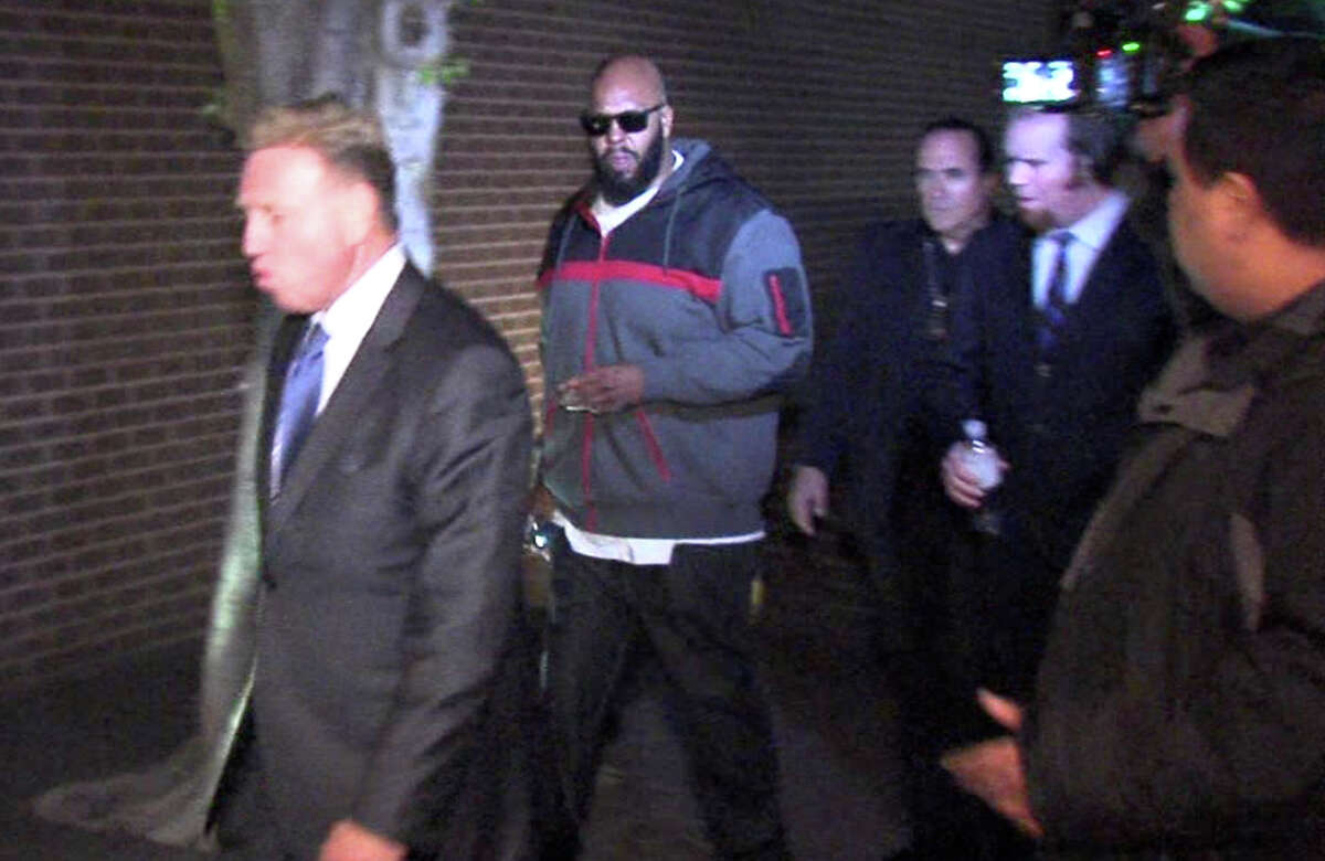 """Death Row Records founder Marion """"Suge"""" Knight (center) arrives at the Los Angeles County Sheriffs department. His lawyer says Knight accidentally ran over and killed a friend."""