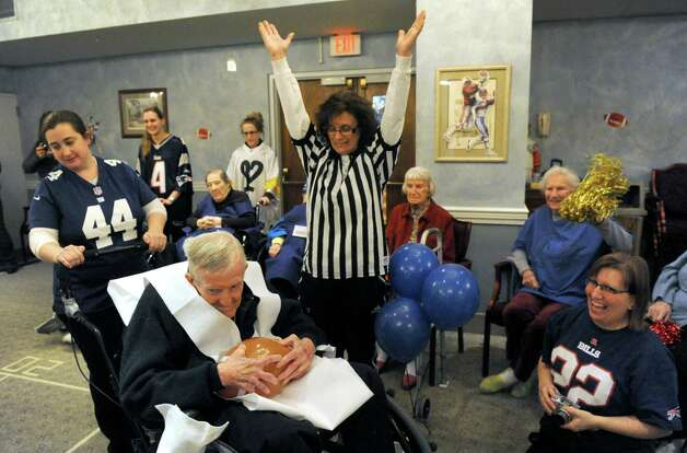Referee Laurie Romand signals for a touchdown as Rev. John Rooney on the Deflate-triots team, pushed by Erin Plonka, rolls into the end zone during the Wheelchair Super Bowl XII at Teresian House on Friday, Jan. 30, 2015, in Albany, N.Y. The Deflate-triots defeated the 12th Man 56-48. (Michael P. Farrell/Times Union) Photo: Michael P. Farrell / 00030409A