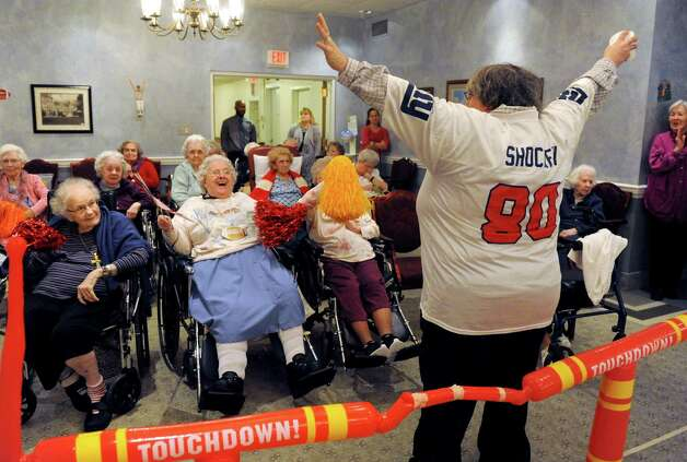 Activities coordinator Cherie Cramer, wearing a Jeremy Shockey jersey, leads the cheer section for the Deflate-triots team during the Wheelchair Super Bowl XII at Teresian House on Friday, Jan. 30, 2015, in Albany, N.Y. The Deflate-triots defeated the 12th man team 56-48. (Michael P. Farrell/Times Union) Photo: Michael P. Farrell / 00030409A
