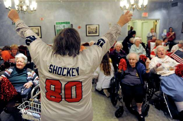 Activities coordinator Cherie Cramer, wearing a Jeremy Shockey jersey, leads the cheer section for the Deflate-triots team during the Wheelchair Super Bowl XII at Teresian House on Friday, Jan. 30, 2015, in Albany, N.Y. The Deflate-triots defeated the 12th man team 56-48.(Michael P. Farrell/Times Union) Photo: Michael P. Farrell / 00030409A
