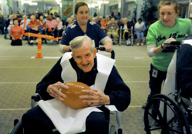 Rev. John Rooney on the Deflate-triots team, pushed by Erin Plonka, breaks for a gain during the Wheelchair Super Bowl XII at Teresian House on Friday, Jan. 30, 2015, in Albany, N.Y. The Deflate-triots defeated the 12th Man 56-48. (Michael P. Farrell/Times Union) Photo: Michael P. Farrell / 00030409A