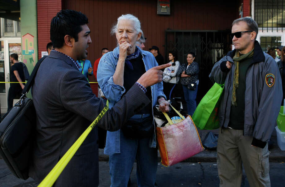 Manish Goyal, of the Office of Economic and Workforce Development (left), speaks with Karen van Dine about recovering her belongings after the fire. Photo: Jessica Christian / The Chronicle / ONLINE_YES