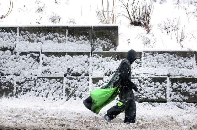 Luis Oyola of Troy walks down Hoosick Street through the snow on Friday Jan. 30, 2015 in Troy, N.Y. (Michael P. Farrell/Times Union) Photo: Michael P. Farrell