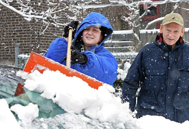 Leanne Macutek, left, clears snow from her father Joseph Macutek's car on First Street Friday Jan. 30, 2015, in Troy, NY.  (John Carl D'Annibale / Times Union) Photo: John Carl D'Annibale