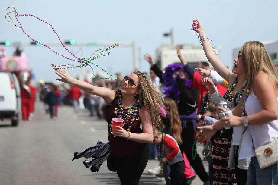 Fans catch beads at the Mystic Krewe of Aquarius' 2014l Mardi Gras Parade in Galveston. Photo: Mayra Beltran, Staff / © 2014 Houston Chronicle