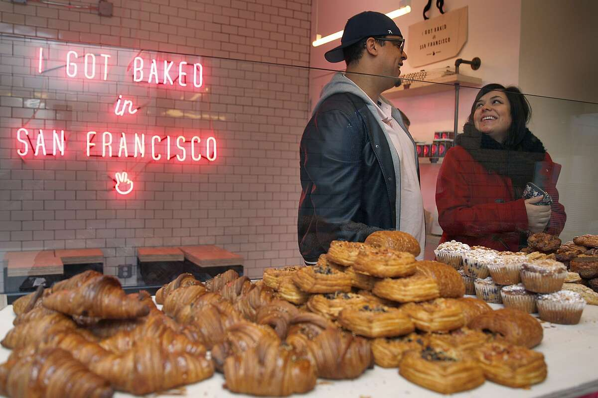 Olinge Lotane-Makalani (middle left) and Elizabeth Santos (right) both from San Francisco wait for their cherry almond muffin and flake croissant from Mr. Holmes Bakehouse in San Francisco, Calif., on Tuesday, January 27, 2015.