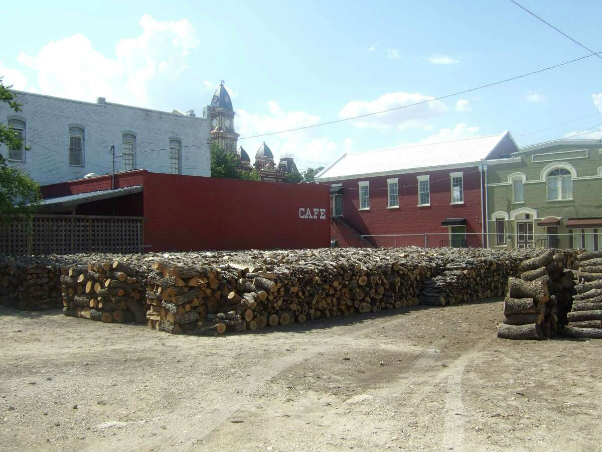 Stacks of post oak wood being air dried at Smitty's market in Lockhart, Texas.