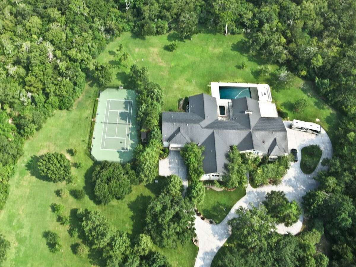 405 Spreading Oaks: This estate in Friendswood is an entertainment retreat with 6 bedrooms, a sports bar, athletic court, game room, pool and 10 tree-filled acres to roam.