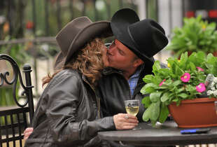 A couple of newlyweds share a kiss in the Wine Garden at the San Antonio Stock Show & Rodeo.