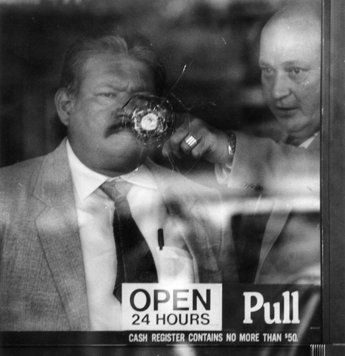 November 20, 1991: Bexar County sheriff investigators inspect a spot where a bullet hit the door of a Stop & Go at Montgomery and New World. Two people were injured in the shooting.