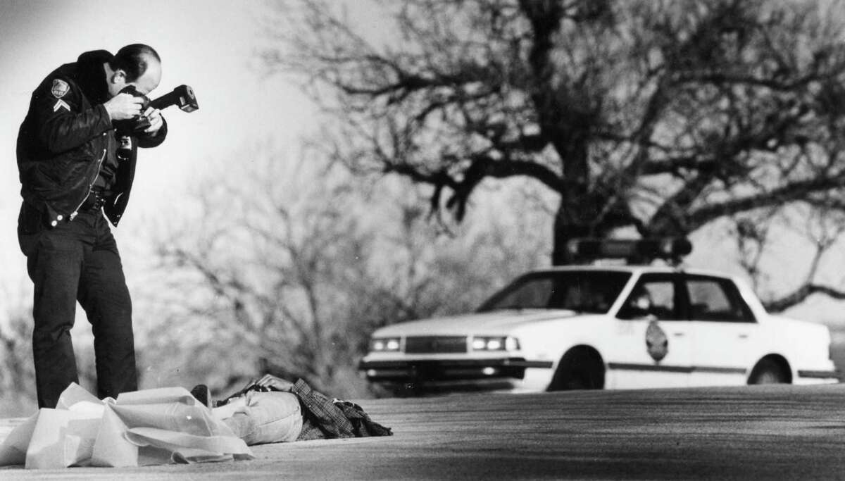 January 20, 1992: A San Antonio Police Department photographer takes pictures after a fatal shooting on a Monday afternoon.