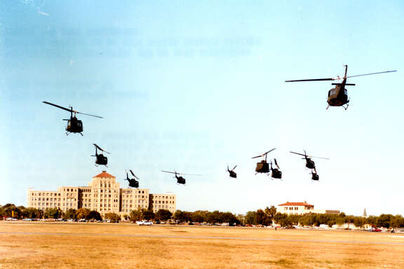 With the original BAMC as a backdrop, Combat Casualty Care Course training participants are flown from Fort Sam Houston to Camp Bullis in 1980.
