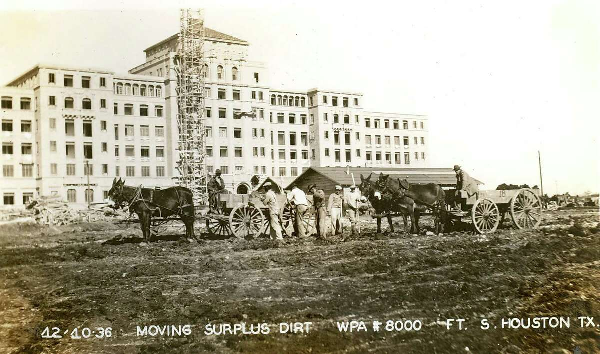 Horse-drawn wagons move surplus dirt outside Station Hospital, which later would become Brooke Army Medical Center, in the final days of 1936. A scaffold stands outside the structure.