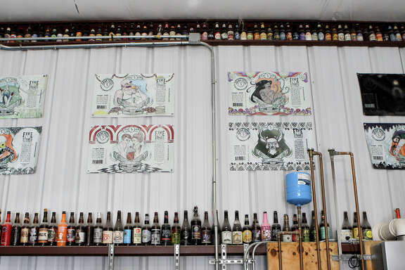 Reproductions of 5 Stones Artisan Brewery's beer bottle labels on the wall at the brewery in Cibolo.