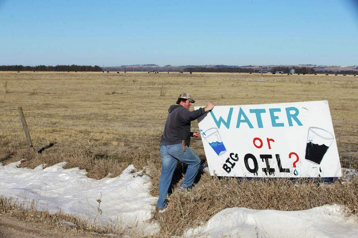 Land owner Jim Tarnick of Fullerton, Neb., who opposes the Keystone XL pipeline, hangs on to an anti-Keystone XL pipeline sign at the site where the planned pipeline is to go through his land, Friday, Jan. 16, 2015. The White House has threatened to veto several bills the Republicans have prioritized, including approving construction of the Keystone XL oil pipeline. (AP Photo/Nati Harnik)