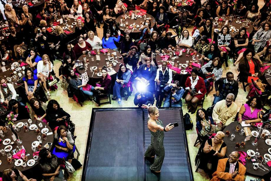 "A model stops to pose for a ""selfie"" while strutting the runway at the NFL Players' Wives Fashion Show Friday, January 30, 2015, in Scottsdale, Arizona. Proceeds benefited the Fresh Start Women's Foundation and The Kwamie Lassiter Foundation, Inc. Photo: JORDAN STEAD, SEATTLEPI.COM / SEATTLEPI.COM"