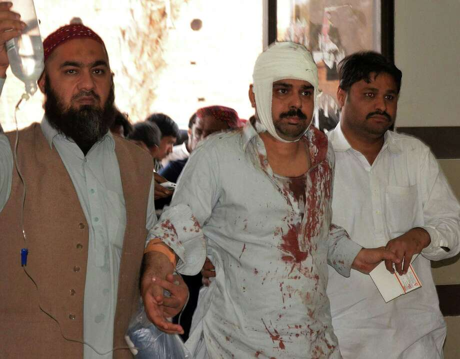 Pakistani relatives help an injured blast victim Friday at a hospital after a bomb explosion ripped through a Shiite Muslim mosque. Photo: FIDA HUSSAIN, Stringer / AFP
