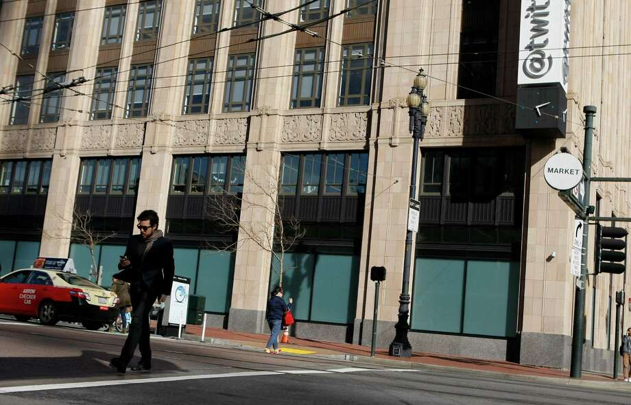 A pedestrian crosses the street in front of the Twitter building that was the old Western Furniture Exchange and Merchandise Mart on Market Street on April 25, 2014 in San Francisco, Calif.  Tech companies are buying historic buildings within the city thus helping to protect these landmarks. Photo: Codi Mills / The Chronicle / ONLINE_YES