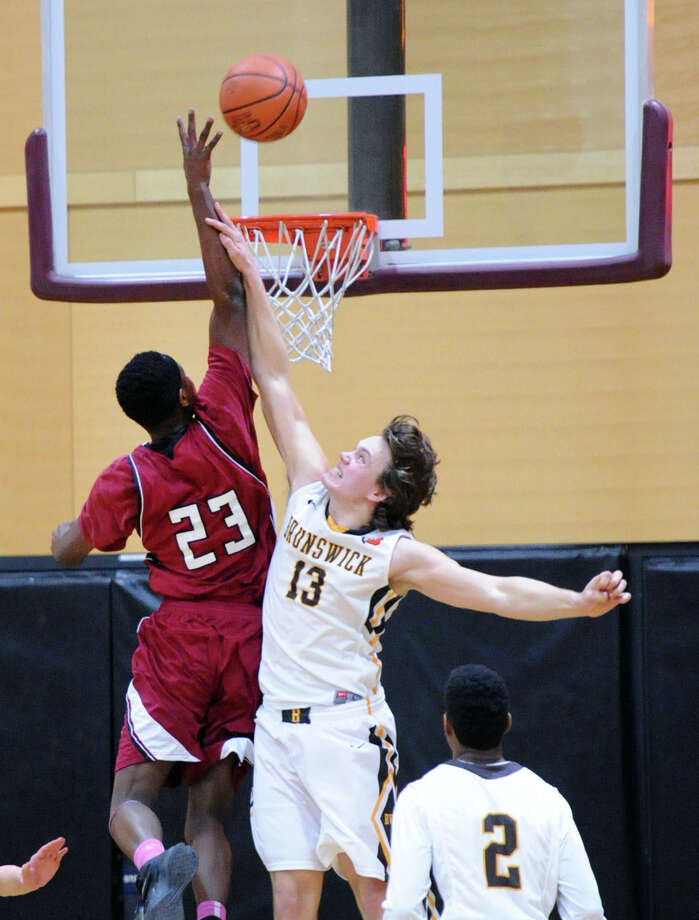 At left, Walter Whyte (#23) of St. Luke's taps in an offensive rebound over Brunswick's Matt Gendell (#13) during the boys high school basketball game between St. Luke's and Brunswick School at St. Luke's in New Canaan, Conn., Friday night, Jan. 30, 2015. Photo: Bob Luckey / Greenwich Time
