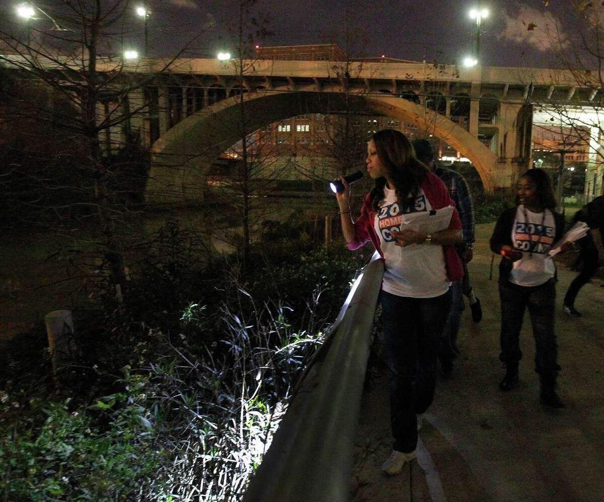 Social worker Kenisha Reaux shines her light into the brush near Buffalo Bayou looking for street people as she and a team of other social workers from the Veterans Affairs Hospital walked downtown during the annual homeless census.