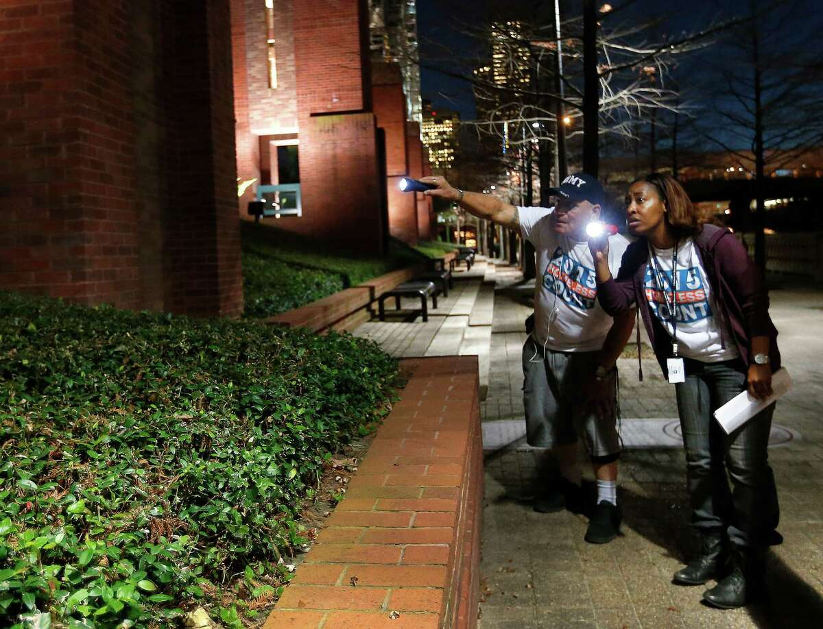 Veteran volunteer Steve Madueno, and social worker Britney Williams shine their flashlights into the hedges around Buffalo Bayou, as they and a team of other social workers from the VA hospital walked downtown during the annual homeless census, Thursday, Jan. 29, 2015, in Houston.