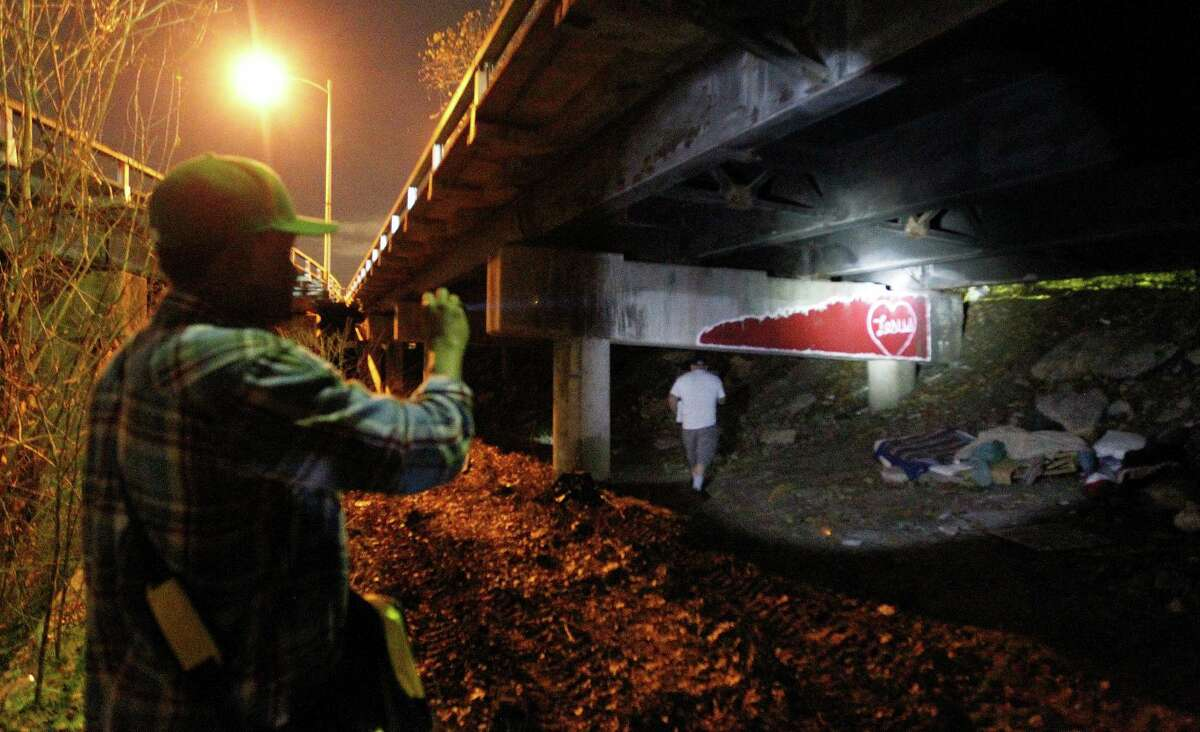 Social worker Harry Low shines his flashlight under the Elysian Street bridge looking for the homeless with a team of other social workers from the VA hospital walked downtown during the annual homeless census, Thursday, Jan. 29, 2015, in Houston.