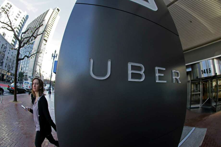 In this Tuesday, Dec. 16, 2014 photo, a woman leaves the headquarters of Uber in San Francisco. (AP Photo/Eric Risberg) Photo: Eric Risberg, STF / AP