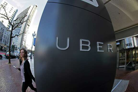 In this Tuesday, Dec. 16, 2014 photo, a woman leaves the headquarters of Uber in San Francisco. (AP Photo/Eric Risberg)