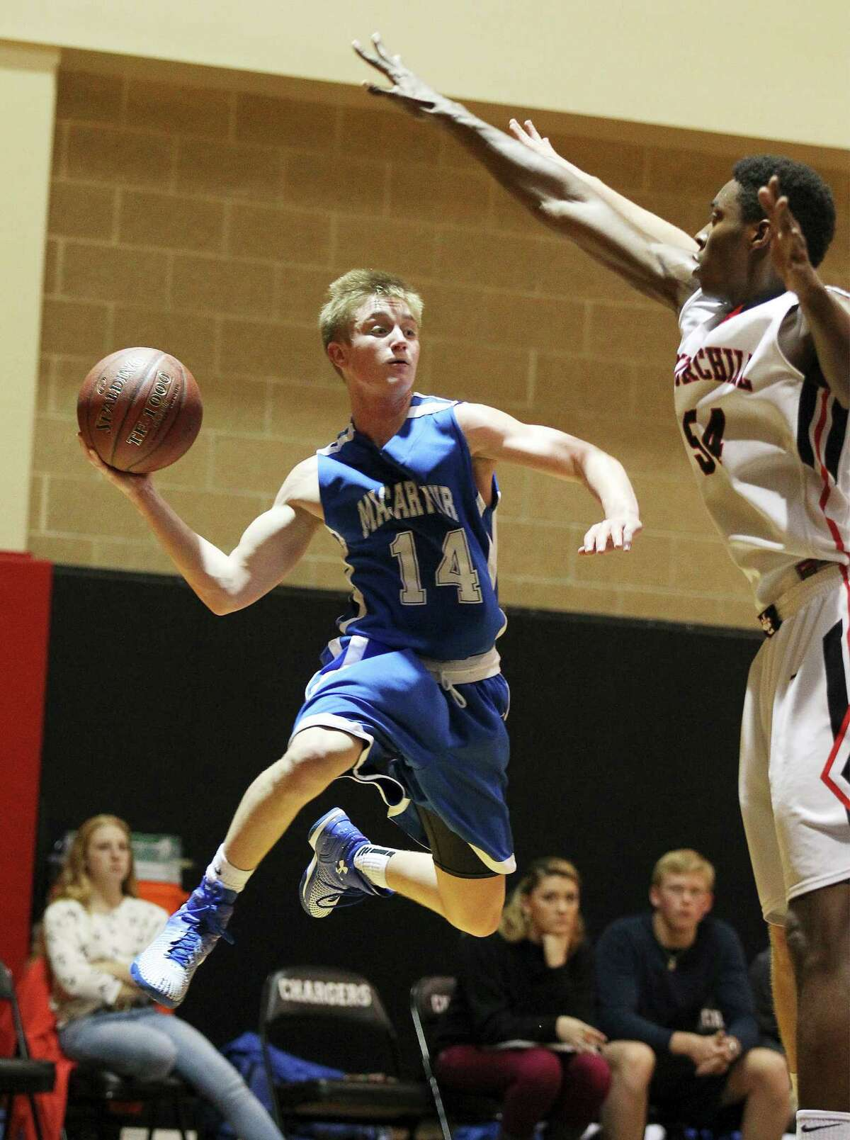 MacArthur's Kyle Murphy (14) attempts a pass against Churchill's Clevon Brown (54) in District 26-6A boys basketball at Churchill on Jan. 30, 2015.