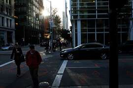 Pedestrians cross at the corner of Mission and 2nd streets in San Francisco, Calif., Friday January 30, 2015.