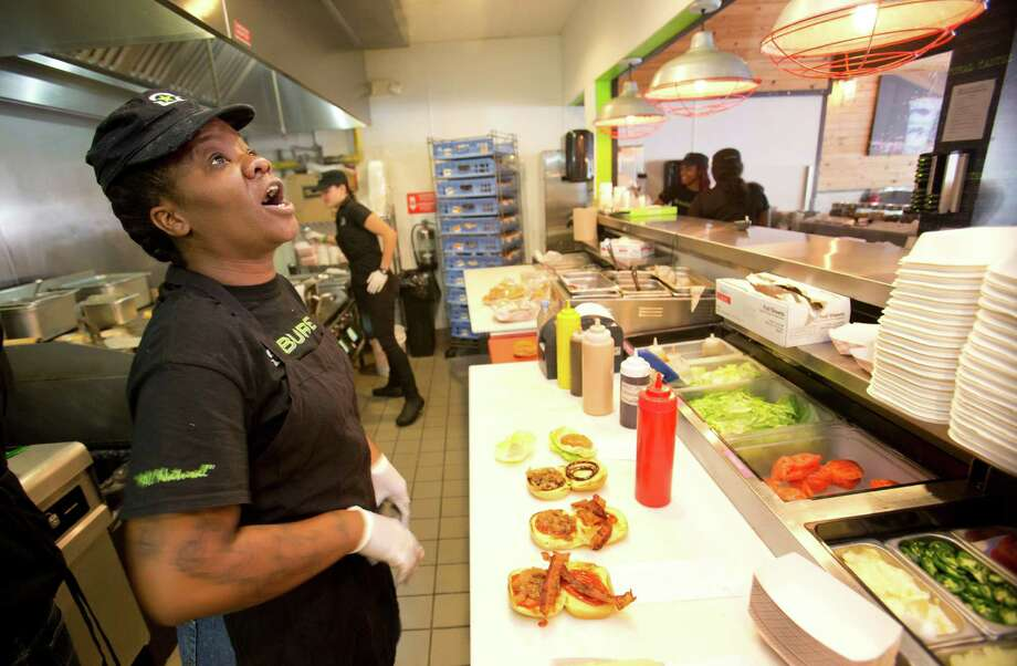 In this Tuesday, Jan. 27, 2015 photo, BurgerFi restaurant employee Nathali Dorvil calls out an order as Elia Carranza, rear, mans the grill at the Aventura, Fla., restaurant. The company plans to nearly double in size from their existing 65 restaurants this year. (AP Photo/Wilfredo Lee) Photo: Wilfredo Lee, STF / AP