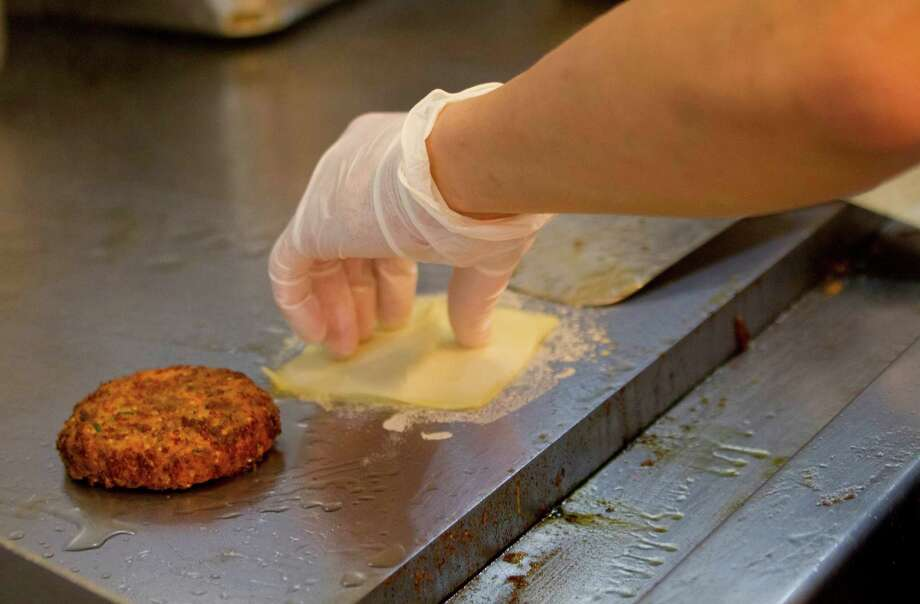 A restaurant employee prepares to add cheese to a veggie burger at a restaurant in Aventura, Fla. Vegetarian products were most likely to be missing ingredients named on their labels, according to a new study of the burger industry by Clear Labs. Photo: Wilfredo Lee, STF / AP