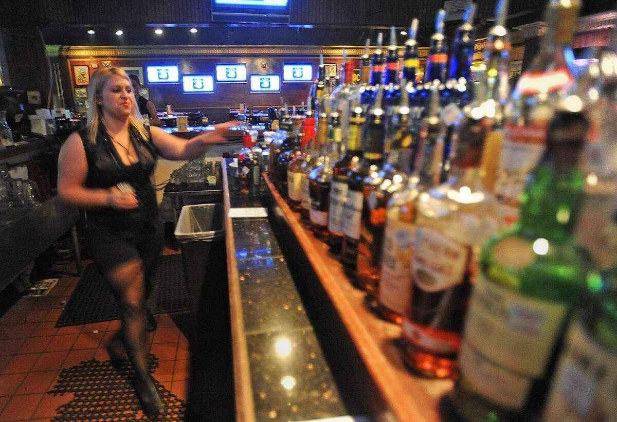 Hillary Wade tends bar at Fast Eddie's in Beaumont on Monday night. The establishment now shows UFC matches on television. Photo taken Monday, November 14, 2011 Guiseppe Barranco/The Enterprise