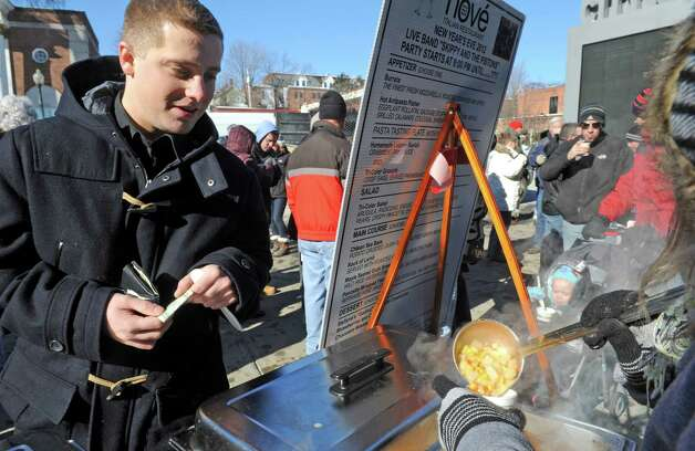 Connor Neal of South Glens Falls waits for Brandy Englehart to pour some of Nove's glutin free corn chowder during the 17th Annual Saratogaa€™s Chowderfest on Saturday Jan. 31, 2015 in Saratoga Springs, N.Y. (Michael P. Farrell/Times Union) Photo: Michael P. Farrell / 00030395A