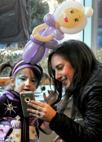 Four-year-old Aubrey Zito checks out a photograph her mother Tricia Zito took of her in her face paints and ballon hat made by Balloon Gal Jenny at the City Center during the 17th Annual Saratogaa€™s Chowderfest on Saturday Jan. 31, 2015 in Saratoga Springs, N.Y. (Michael P. Farrell/Times Union) Photo: Michael P. Farrell / 00030395A
