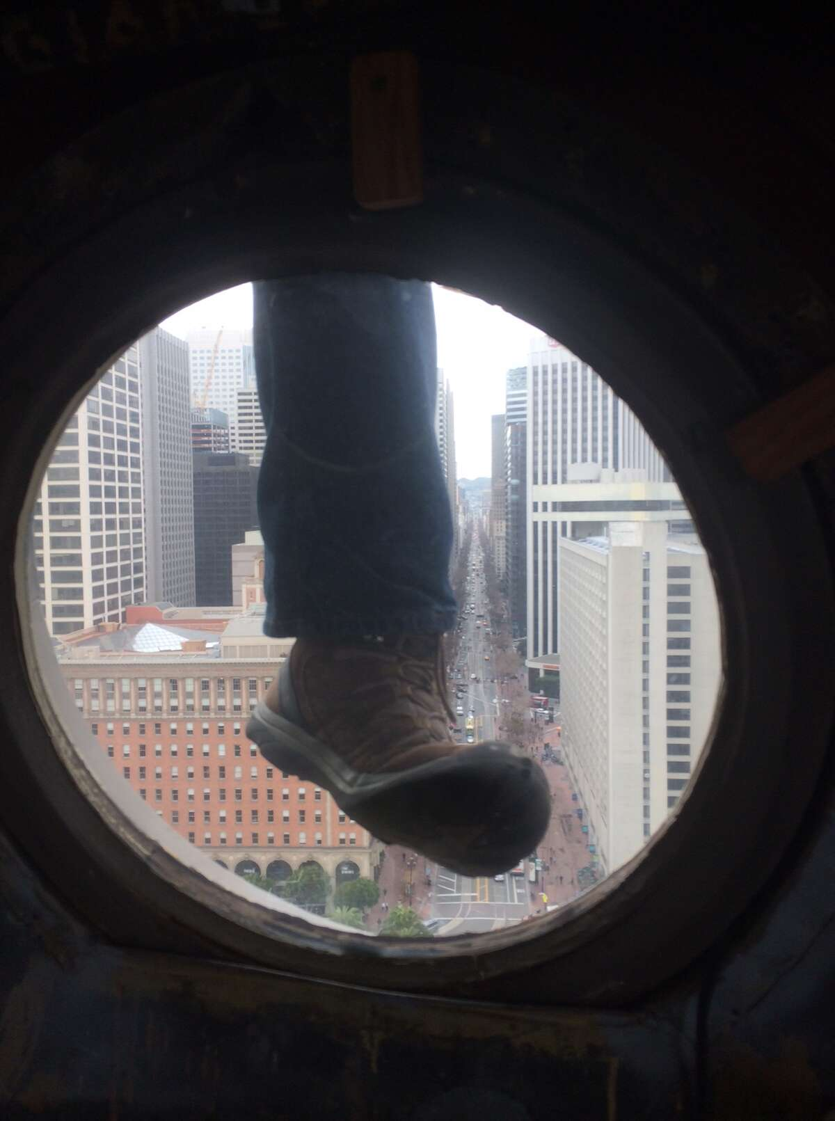 Steeplejack Jim Phelan climbs on the outside of the Ferry Building. The view is 240-feet up looking straight down Market Street.