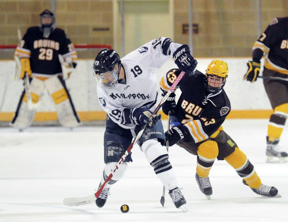 At far left, Brunswick goalie Brian Ketchabaw (#29) looks on as Millbrook player Jacob Moreau (#19), center, and Brunswick's Eric Ganshaw (#23), right, fight for a loose puck during the boys high school ice hockey game bewteen Brunswick School and Millbrook School at Brunswick in Greenwich, Conn., Saturday, Jan. 31, 2015. Photo: Bob Luckey / Greenwich Time