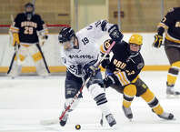 At far left, Brunswick goalie Brian Ketchabaw (#29) looks on as Millbrook player Jacob Moreau (#19), center, and Brunswick's Eric Ganshaw (#23), right, fight for a loose puck during the boys high school ice hockey game bewteen Brunswick School and Millbrook School at Brunswick in Greenwich, Conn., Saturday, Jan. 31, 2015.