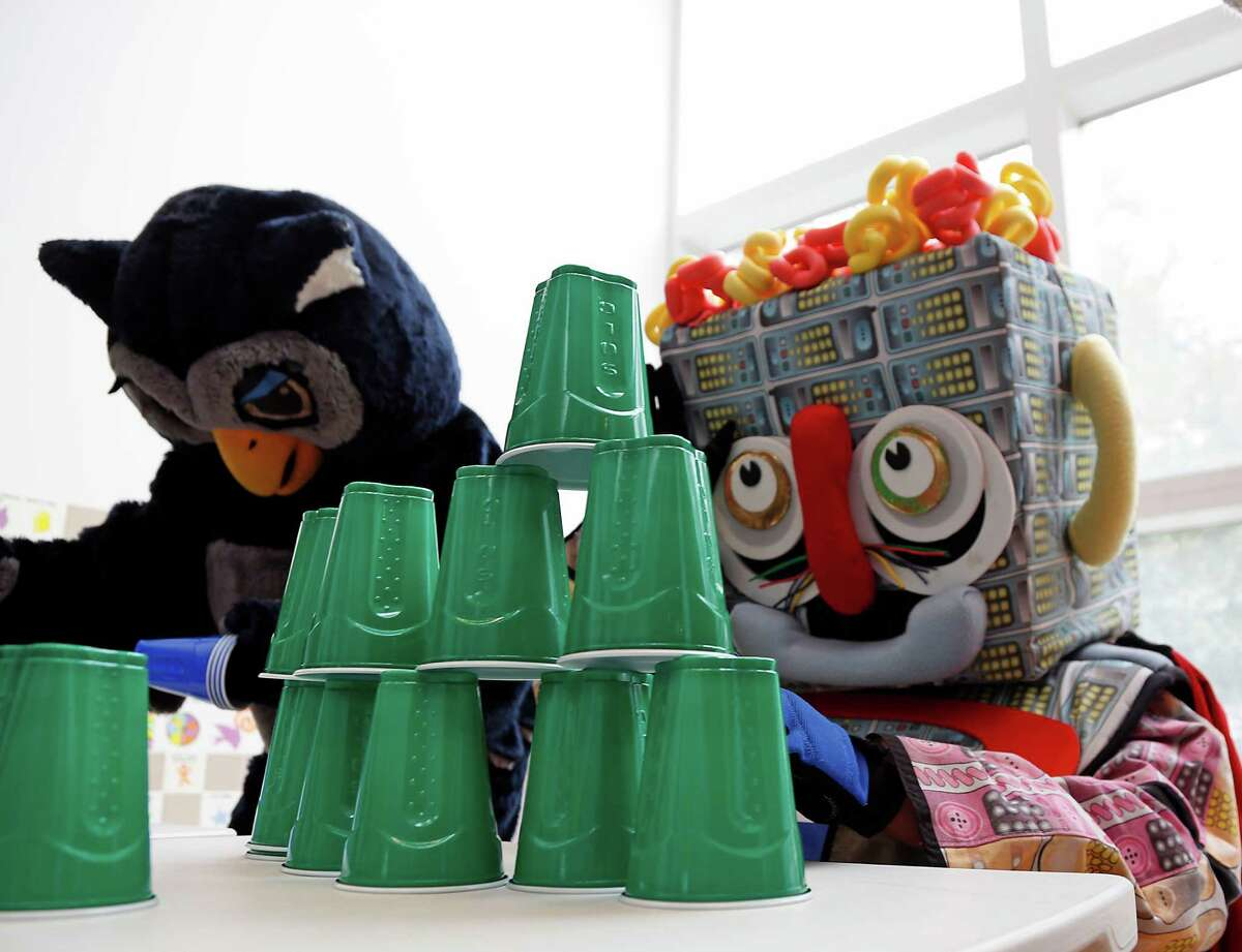 Rice University's Sammy the Owl, left, the Children's Museum of Houston's Telephone Man right, compete in a cup stacking contest during the Children's Museum of Houston Mascot Races Saturday, Jan. 31, 2015, in Houston. The event is part of the Museum's Have a Ball WonderWeek, which celebrates all sports in time for Super Bowl Sunday.