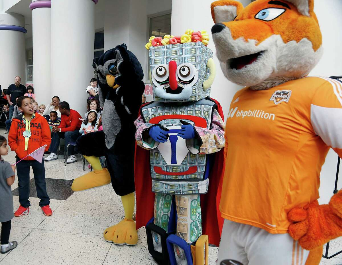Eric Stricker left, looks on during the Children's Museum of Houston Mascot Races featuring Rice University's Sammy the Owl 2nd from left, the Children's Museum of Houston's Telephone Man 2nd from right, and the Houston Dynamo's Diesel right, Saturday, Jan. 31, 2015, in Houston.