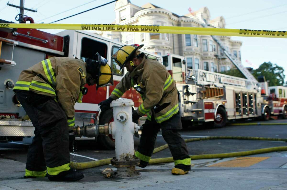 Firefighters unscrew fire hoses from hydrants after battling a four-alarm fire which damaged 17 units in four residential buildings on the 1500 block of McAllister Street between Divisadaro and Scott streets in San Francisco, Calif. Saturday, January 31, 2015.