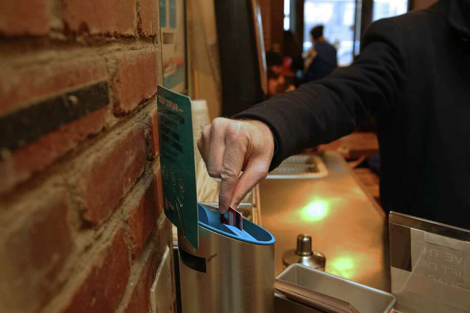 A customer uses DipJar to charge his credit card a $1 tip at Dos Toros Taqueria in New York. Increasing varieties of digital payment options are expanding when and how much people are expected to tip. Photo: NICOLE BENGIVENO, STF / NYTNS