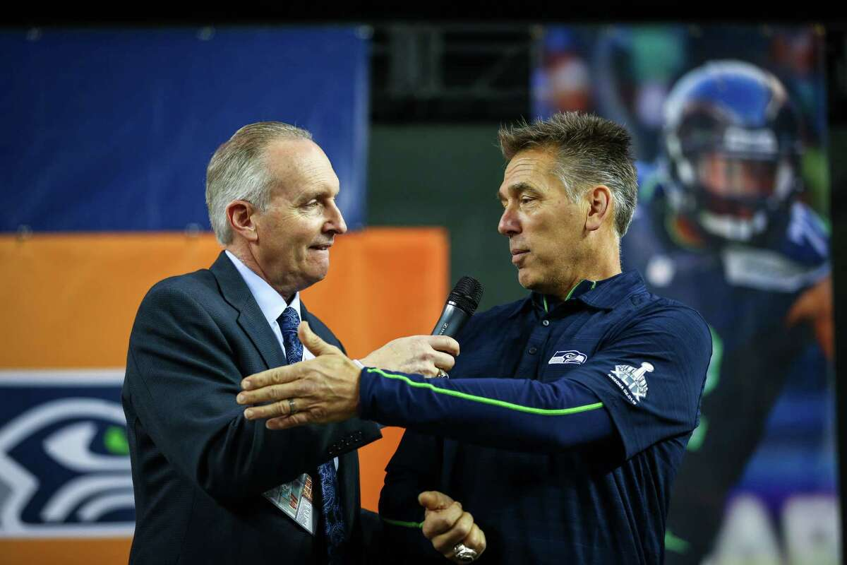 Announcer Steve Raible greets former Seahawks player Jim Zorn on the stage during the Seattle Seahawks Fan Fest at Chase Field in downtown Phoenix. The 12th Man celebration brought tens of thousands of rowdy Seahawks fans downtown, the day before the Seahawks play the New England Patriots in Super Bowl 49. The fan party featured the Sea Gals, Blue Thunder, the team mascots and more. Photographed on Saturday, January 31, 2015.