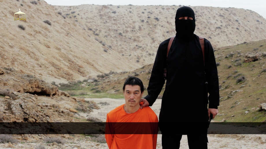 This image made from a video released by Islamic State militants on Saturday purports to show a militant standing next to Japanese journalist Kenji Goto before his beheading, an act condemned by the West.  Photo: HONS / Islamic State group