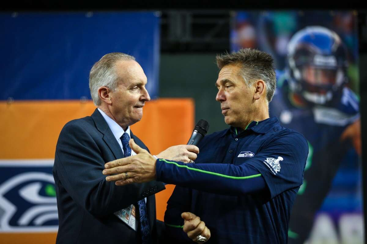 Announcer Steve Raible greets former Seahawks player Jim Zorn on the stage during the Seattle Seahawks Fan Fest at Chase Field in downtown Phoenix. The 12th Man celebration brought tens of thousands of rowdy Seahawks fans downtown, the day before the Seahawks play the New England Patriots in Super Bowl 49. The fan party featured the Sea Gals, Blue Thunder, the team mascots and more. Photographed on Saturday, January 31, 2015. (Joshua Trujillo, seattlepi.com)