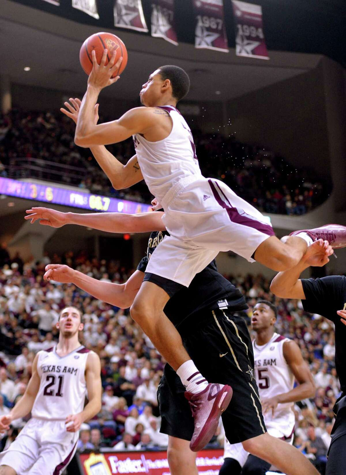 Texas A&M guard Jordan Green, top, goes strong to the basket and draws a foul from Vanderbilt's Luke Kornet during the first half.